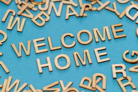 Wooden letters WELCOME HOME on blue background