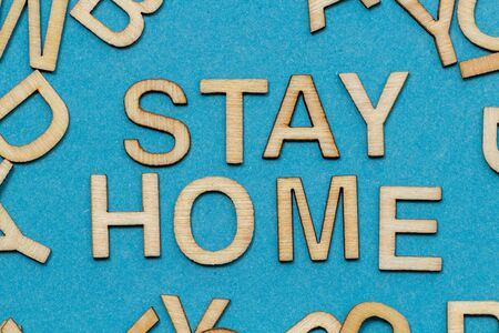 Wooden letters STAY HOME on blue background