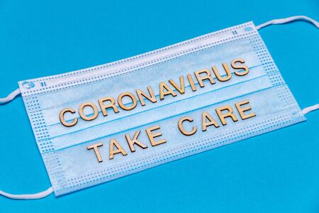 Wooden letters CORONAVIRUS TAKE CARE on protective medical mask.Corona virus concept. Stock Photo