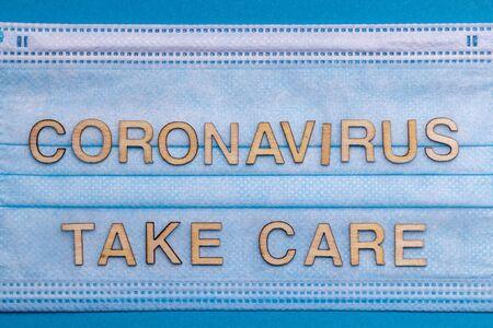 Wooden letters CORONAVIRUS TAKE CARE on protective medical mask.Corona virus concept Stock Photo
