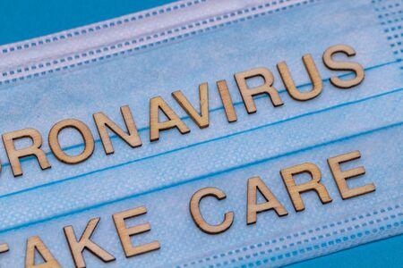 Wooden letters CORONAVIRUS TAKE CARE on protective medical mask.Coronavirus concept.