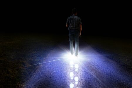 Man walking with light foot prints on a road at night