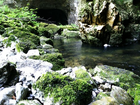 collapsed: River inside a cave with collapsed roof and one of cave entrances behind.