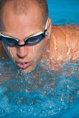 Man swims with swimming goggles.