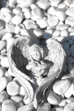 whitem: White stone cherub resting on a stone.