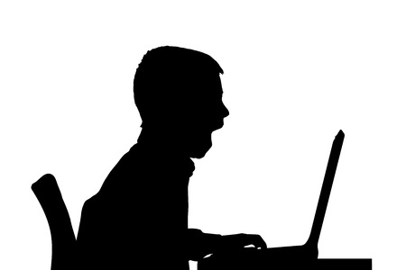 Vector silhouette of a boy sitting at a computer on a white background. Vector