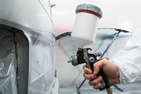 Painter spray gun in the hands of a painter. Stock Photo