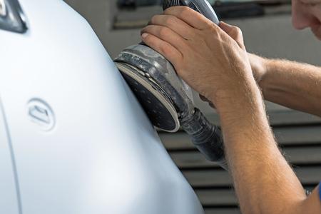 車の店で車のニスを研ぐ男の手にグラインダー。 写真素材