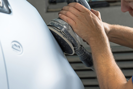 Grinder in the hands of a man who sharpen a car varnish in the car shop.