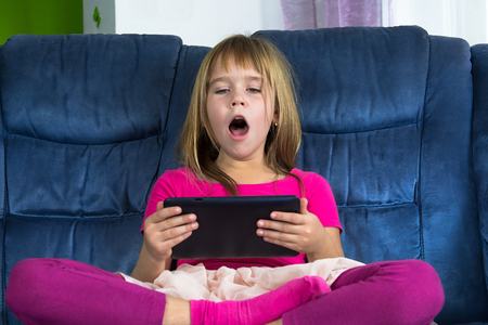 Little girl sitting and play game at mobile phone.