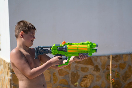 The boy play with water gun in the garden.