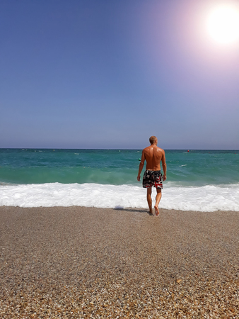 Back view of relaxed young muscular man enjoying sea view.