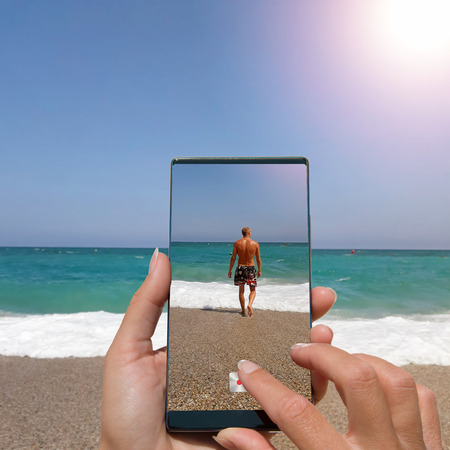 Woman photographing on cell phone muscular man by the sea.