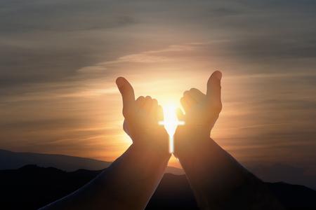 Christelijke man met open handen, zonneschijn in de vorm van een kruisbeeld en dramatische hemel.