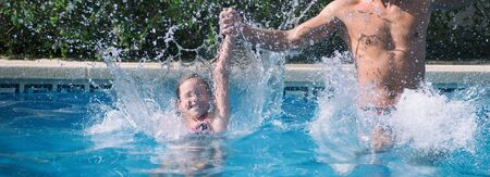 Father and daughter enjoying swimming pool.