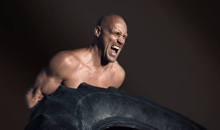 Shirtless man flipping heavy tire outside gym. Workout.