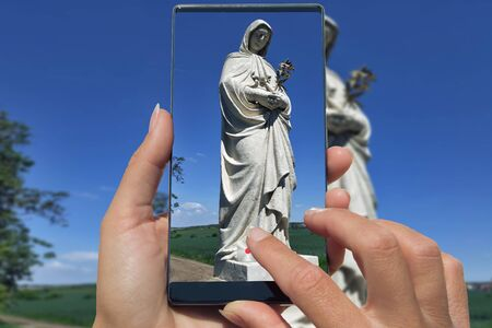 Woman photographing on cell phone statue of Mary praying in nature.