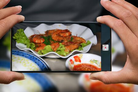 Woman photographing on cell phone grilled shrimps with salad on a plate and red sauce in a restaurant. Imagens