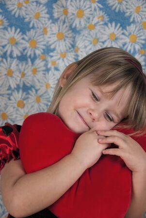 Cute little girl sleeping on heart shaped red pillow. Reklamní fotografie