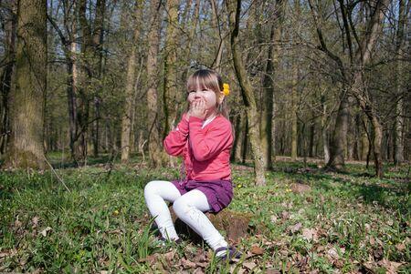 Bambina nella foresta seduta su un ceppo