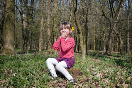 Little girl in the forest sitting on a stump