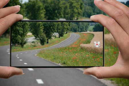 Woman photographing on cell phone empty asphalt road surrounded around field and trees and red flowers.
