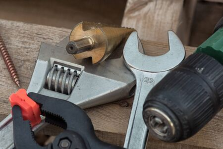 Various tools drill, clamp, wrench, screw, pliers lying on a wooden pallet.