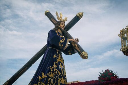 Jésus-Christ portant la croix avec ciel dramatique.