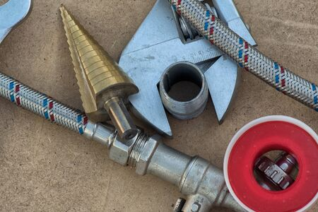 Different things for plumbers lie on ground. Teflon tape, wrench, hose, tube, water tap .