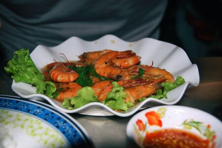 Grilled shrimps with salad on a plate and red sauce in a restaurant.