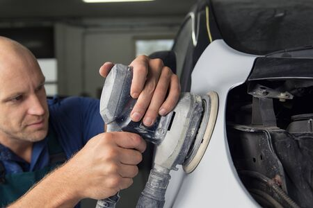 A man who sanding with a grinder and prepares the paint for the car in a car service.