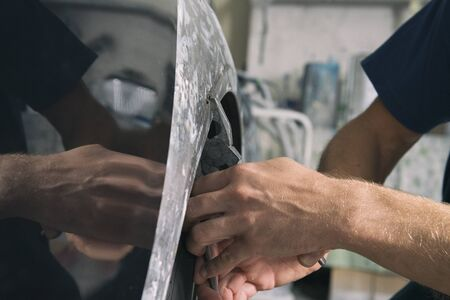 A man who sanding with a grinder and prepares the paint for the car in a car service. Repairman fix car paint. Stockfoto
