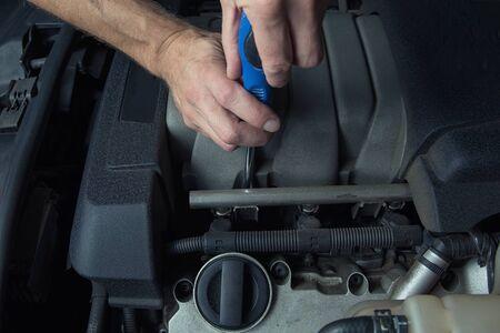 Man fixes car in a car service. Engine repair, maintenance, service.