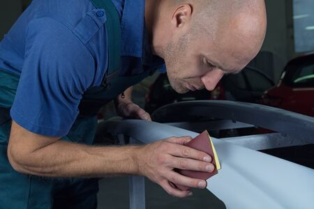 A man who sanding with a grinder and prepares the paint for the car in a car service. 写真素材