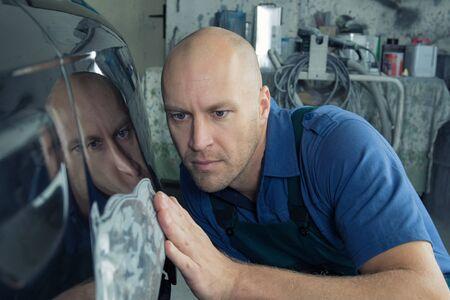 Man fixes car fender after crash and prepares the paint for the car in a car service. Repairman fix car paint.