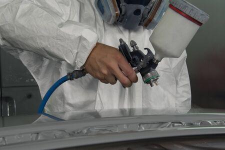 Painter with spray gun sprays the part on the car. Imagens