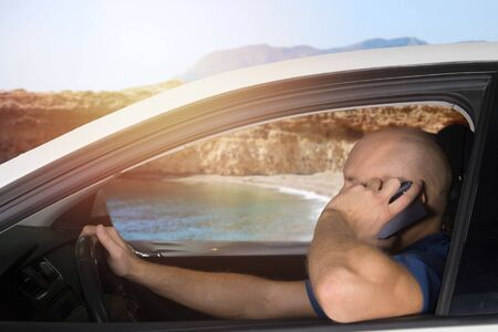 Man driving in car and talking on cell phone. Holiday, vacation, road trip. Stockfoto