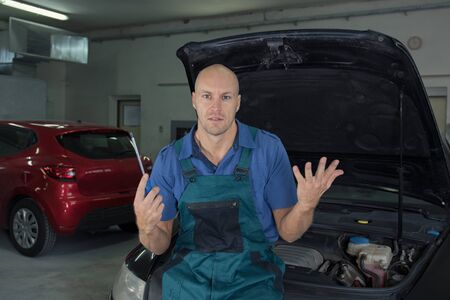Man fixes car in a car service. Engine repair, maintenance, service.