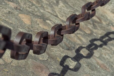 Detail view of vintage rusty chain on the stone ground.