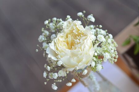 White roses in a vase with decorations on wedding table. Stock Photo