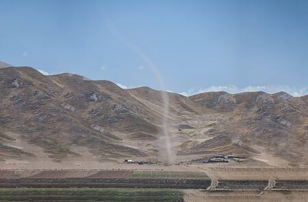 Real tornado in Peru, with farm field and mountains in the background. Фото со стока