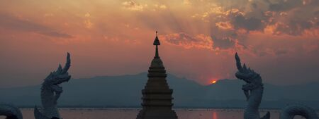 Sunset behind mountains at lake with buddhist temple and dragons in thailand.