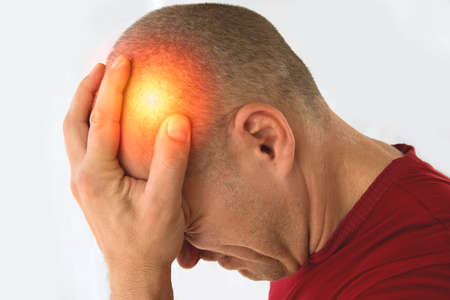 Man isolated on white background suffering from severe headache.