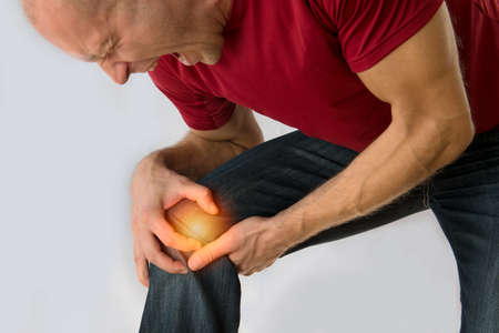 Health care concept man suffering from knee pain on light background.