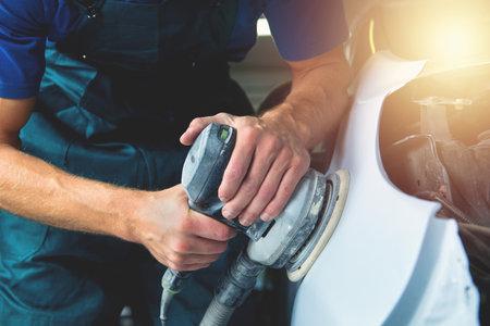 Grinder in the hands. Man sharpen car varnish in the car paint shop. 版權商用圖片