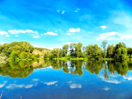 reflexion: Lago con la reflexión, árboles y cielo