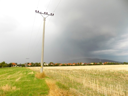 precipitation: Power line column on field and storm over village
