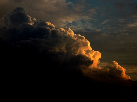convection: Cumulonimbus convective cloud indicating storm formation through low pressure system in unstable atmosphere during summer during sunset