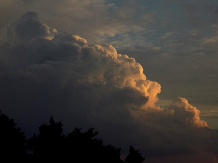 Cumulonimbus convective cloud indicating storm formation through low pressure system in unstable atmosphere during summer during sunset