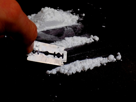 junkie: Junkie preparing cocaine drug powder lines with razor blade Stock Photo